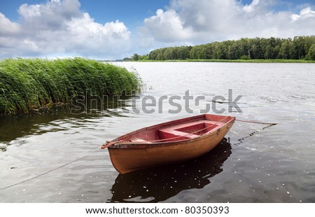 Old lonely fishing floating on the water - stock photo