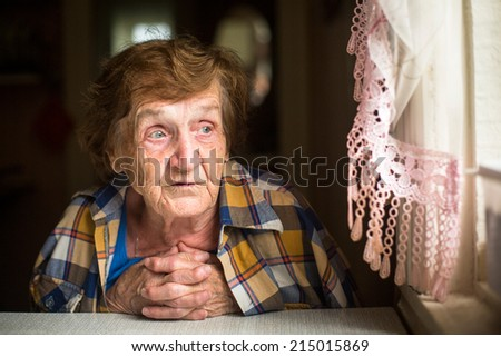 Old lonely woman sitting at a table near the window in his house. Old age. Loneliness.  - stock photo