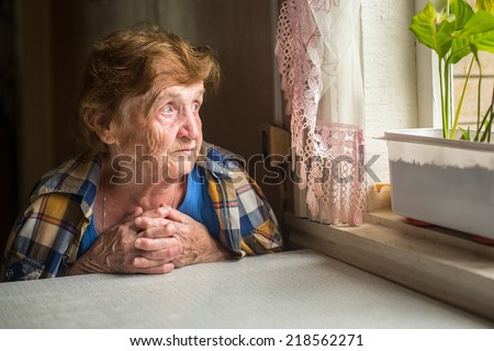 Old lonely woman sitting near the window in his house. - stock photo