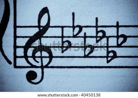 Old-looking blue washed grungy music manuscript with treble clef and key signature of six flats. - stock photo