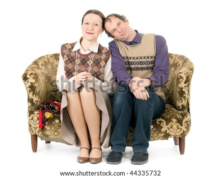 old looking couple in love sitting on retro couch - stock photo