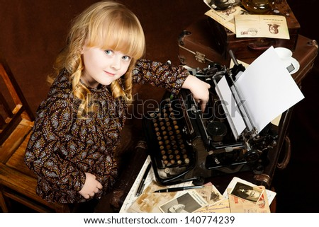 Old-looking image of the small caucasian girl who works at vintage typing machine - stock photo