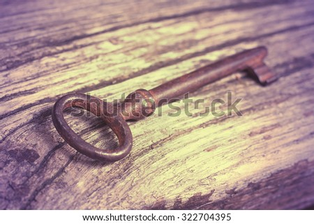 Old lost rusty key lying in the wood - stock photo