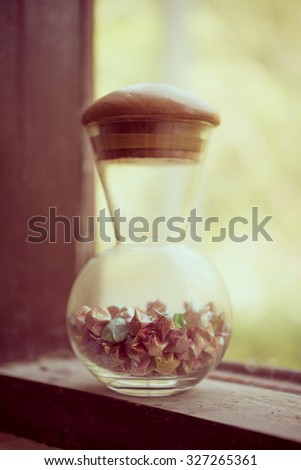 Old luck star and glass bottle beside window - vintage effect picture - stock photo