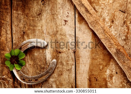 Old lucky horseshoe background with the horseshoe arranged in the corner with a green Irish shamrock for double luck on a rustic wooden background with copyspace - stock photo