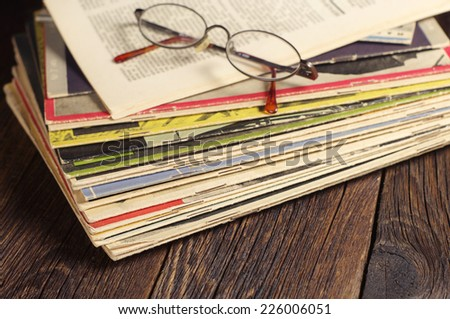 Old magazines and glasses on vintage wooden table - stock photo