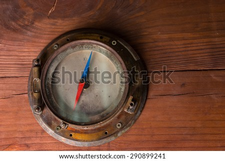 Old magnetic antique brass ships compass mounted on a wooden cabinet for navigating the globe during a cruise or voyage, with copyspace - stock photo