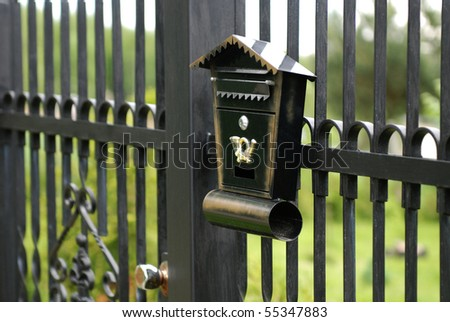 old mailbox fixed to the metal fence - stock photo