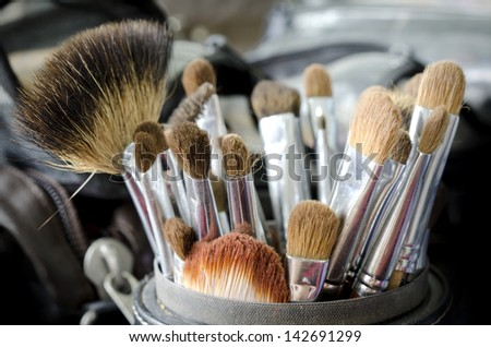Old makeup brushes in holder - stock photo