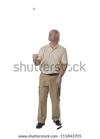 Old male golfer tossing a golf ball in the air - stock photo