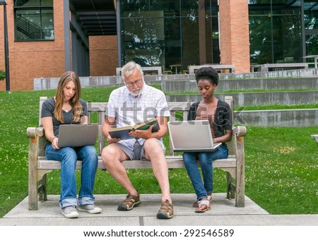Old male student reading book with two mixed race young adult students with computers - stock photo