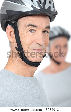 old man and his partner wearing bike helmets