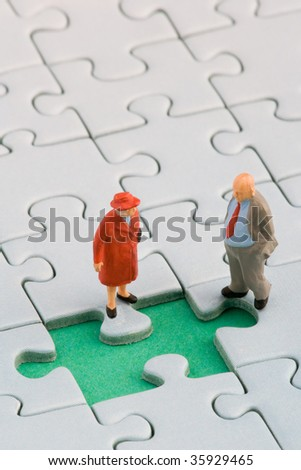 Old man and old woman in front of a missing jigsaw piece - stock photo