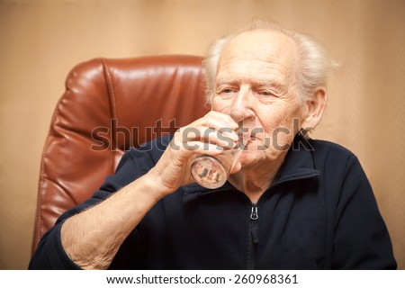 old man drinking a glass of water - stock photo