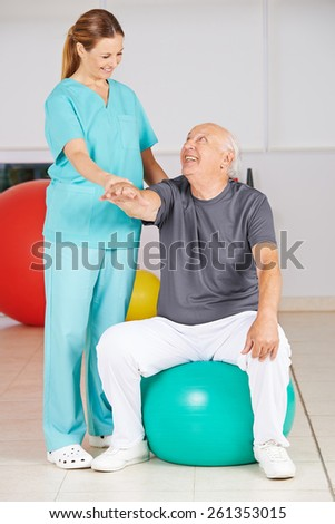 Old man during rehab in physiotherapy in a nursing home - stock photo