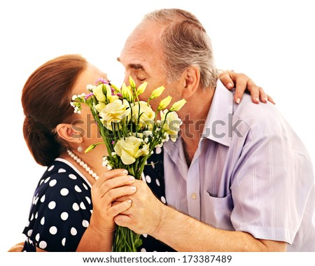 Old man embracing woman . Sharpness on the bouquet - stock photo