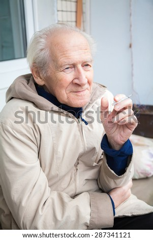 old man enjoying a cigarette - stock photo