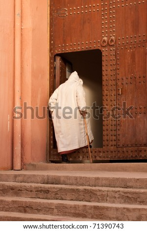 Old man entering a doorway in Morocco - stock photo