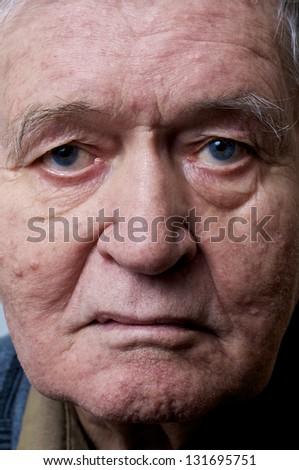 old man face closeup eyes looks at camera - stock photo