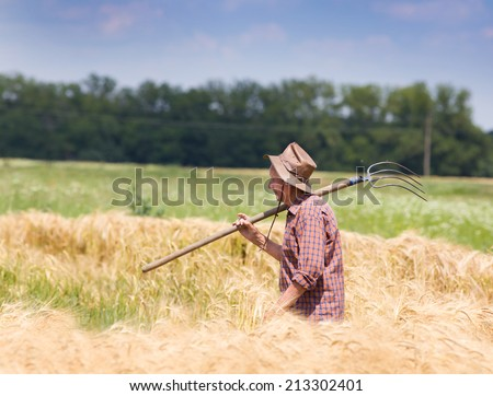 Old man farmer holding fork in barley field after hard work - stock photo
