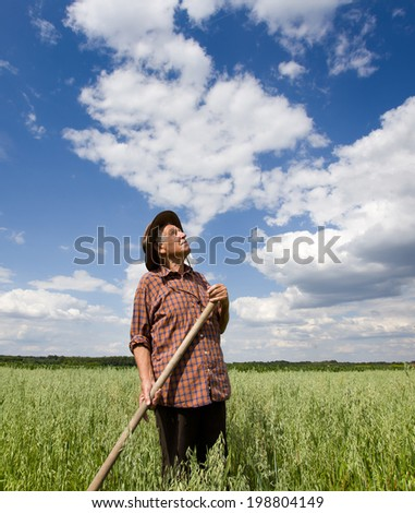 Old man farmer standing in oat field and looking up in sky