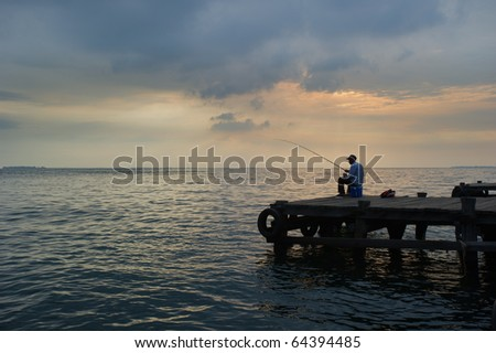 old man fishing at the dock - stock photo