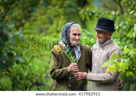 Old man giving flowers to his wife as for valentines day - stock photo