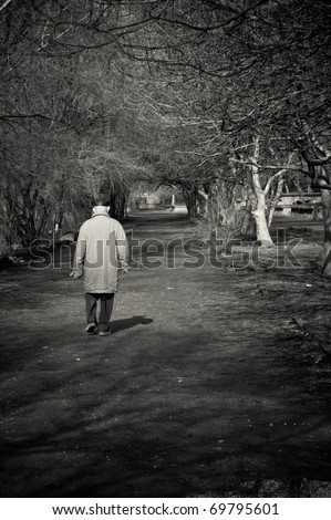 Old man goes alone through the park. Black and white photo - stock photo