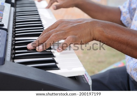 Old man hand playing musical instrument. - stock photo