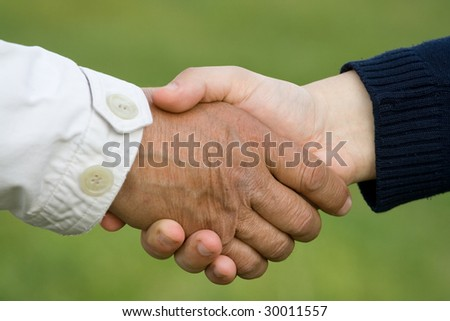 Old man hand shaking with young man - stock photo