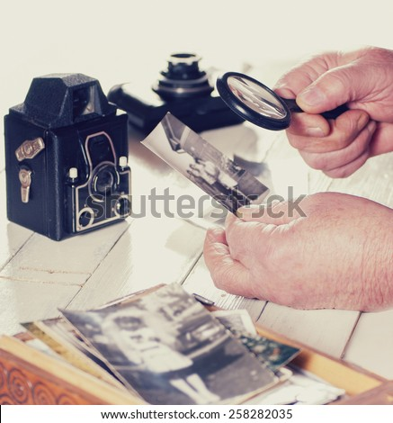 Old man hands, view photos with magnifying glass from the past, retro cameras on the table, filtered photo