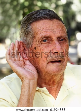 Old man hard of hearing, outdoor - stock photo