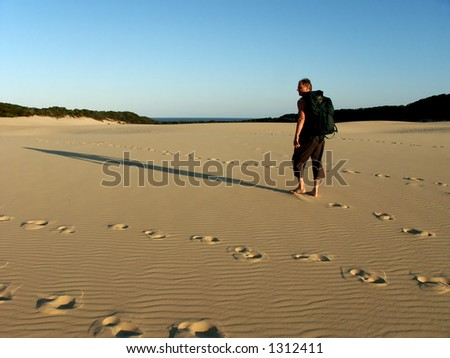old man hiking in sand dunes on fraser island australia - stock photo