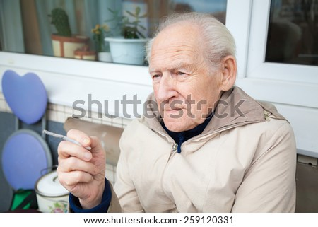old man holding a cigarette sitting on a balcony - stock photo