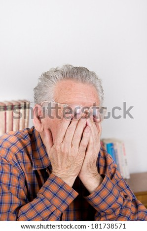 Old man holding hands on eyes under reading glasses - stock photo
