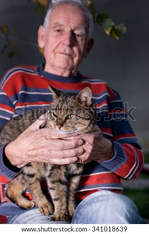 Old man holding tabby cat in the lap in garden - stock photo