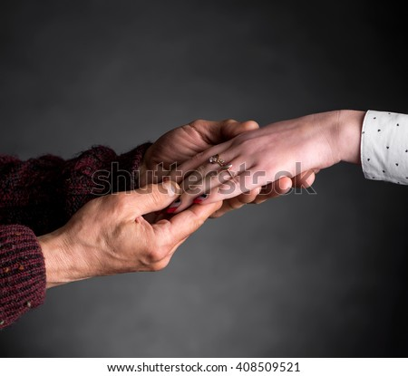 Old man holding young woman's hand on a gray background