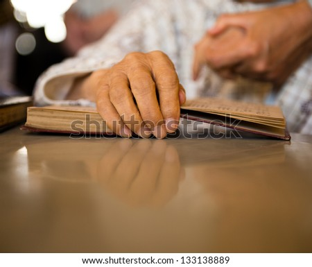 Old man holds a bible in his hands. - stock photo