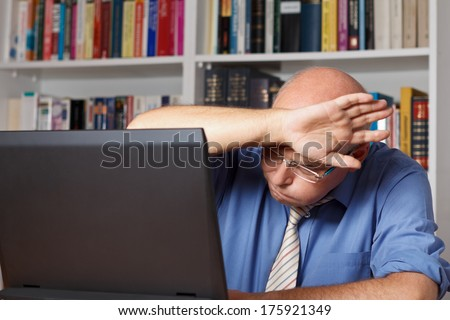 Old man in front of his computer wiping his brow in relief - stock photo