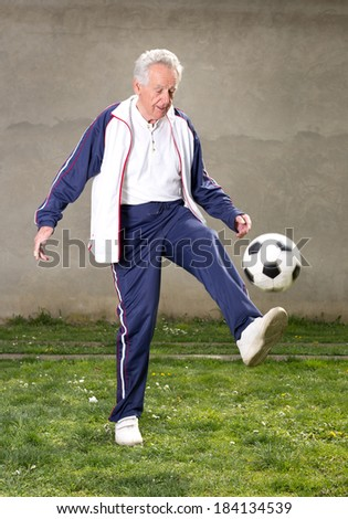 Old man in seventies kicking a soccer ball in courtyard - stock photo