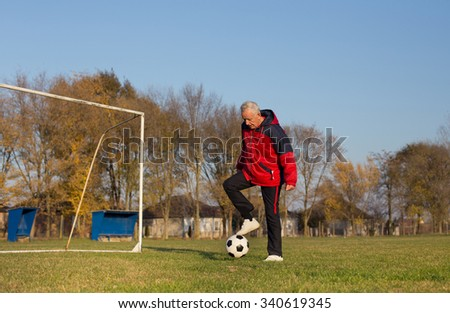 Old man in seventies kicking a soccer ball on playground with goal behind him - stock photo