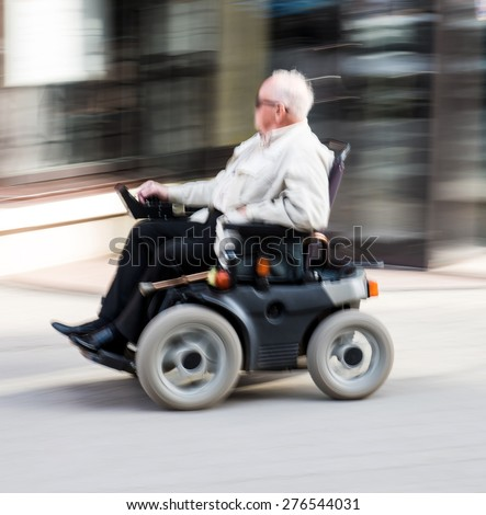 Old man in wheelchair. Intentional motion blur