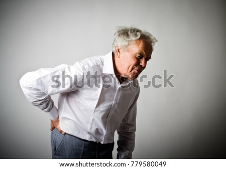 Old man in white is having a back pain.