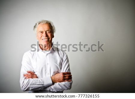 Old man in white is smiling. Portrait of old professional.