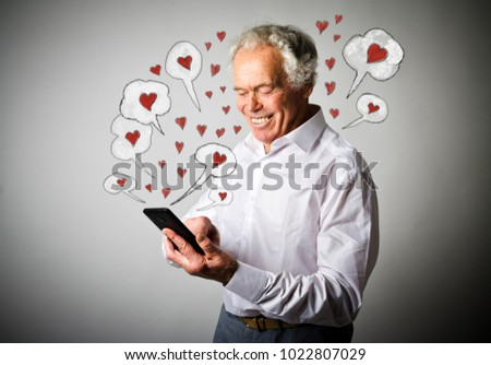 Old man in white is using a smart phone. Valentine day and love concept.