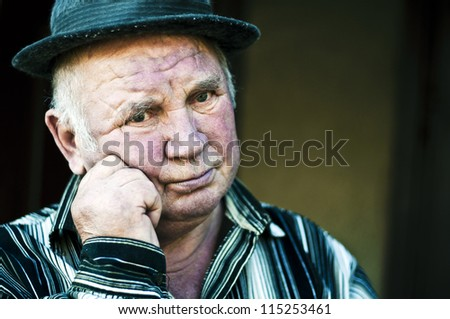 old man keeps his hand near the face - stock photo