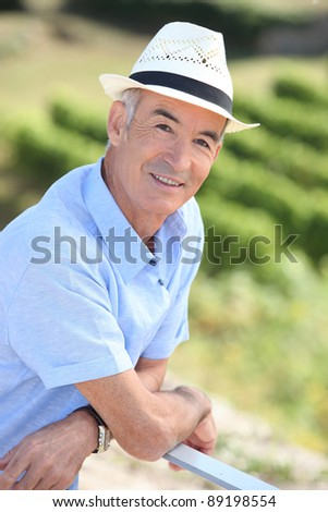 Old man leaning against railing - stock photo