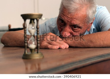 Old man leaning on a table and looking at the hourglass with sadness in his eyes. Concept of life and old age. Selective focus - stock photo