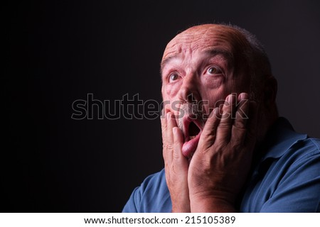 old man looking scared or crazy - stock photo