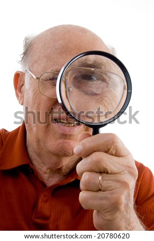 old man looking through lens against white background - stock photo